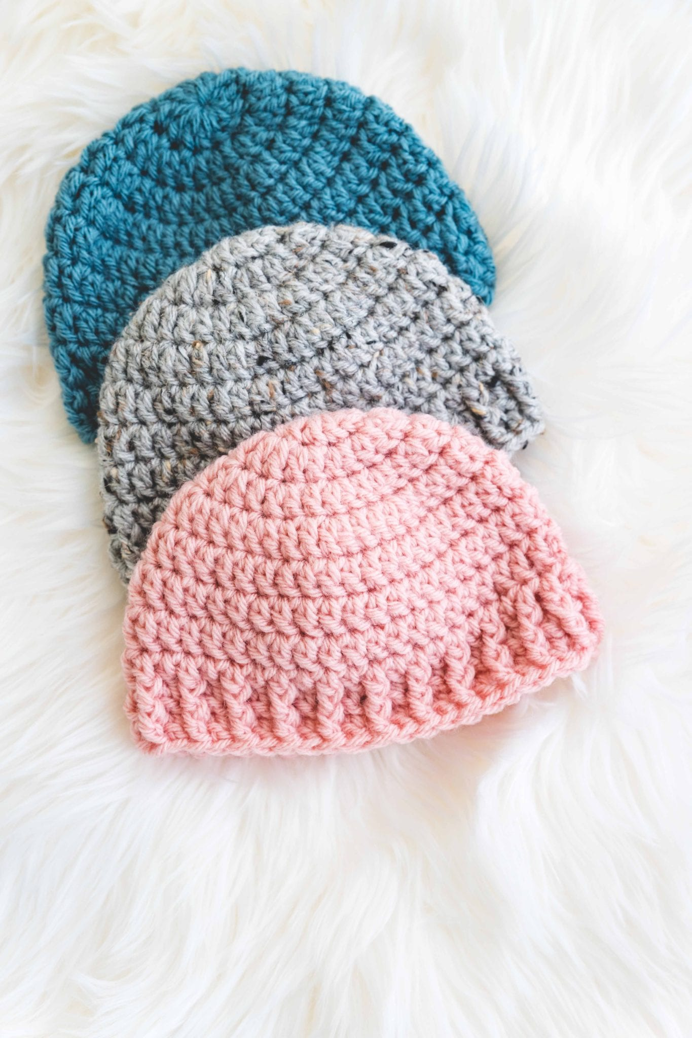 Crochet baby hat with simple stitches and gender neutral ribbing. Made in pink, blue, and grey.
