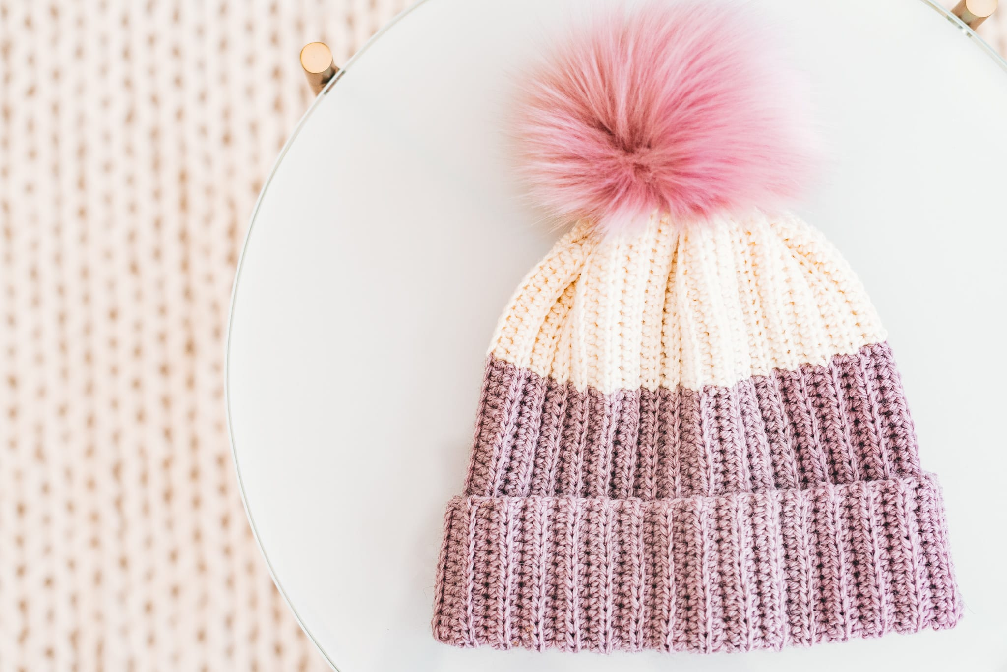 Crochet hat with knit look fabric and a faux fur pom pom